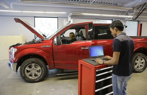 In this photo taken Thursday, Aug. 13, 2015, Nitin Bandaru, right, works on a hackathon project at the Ford Motor Company Research and Innovation Center in Palo Alto, Calif. The convergence of cars and technology is blurring the traditional geographical boundaries of both industries. Silicon Valley is dotted with research labs opened by automakers and suppliers, who are racing to develop high-tech infotainment systems and autonomous cars.