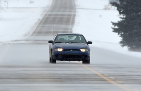 A car drives through the blowing snow on Secondary Highway 651 near Legal, Alta. on Wednesday, Feb. 11, 2015.