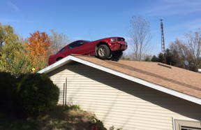 In this Oct. 26, 2015 photo, a Ford Mustang is stopped on a roof of a house in Woodhull Township, Mich. Police say the driver had a medical problem and lost control of his car.