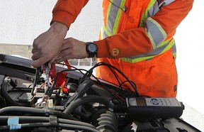 A CAA Manitoba technician prepares to boost a battery at a member's home in West Kildonan.