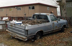 A rusting, unplated pickup truck sits in a Forest Lawn back alley filled with debris.