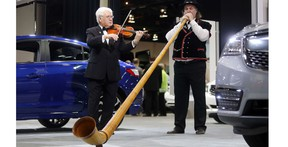 William Hopson of the Calgary Philharmonic plays an alp horn alongside roving violinist Igor Motchalov among the cars and trucks at last year's Vehicles and Violins Gala.