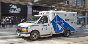 An ambulance races across Queen Street at the Eaton Centre in Toronto.