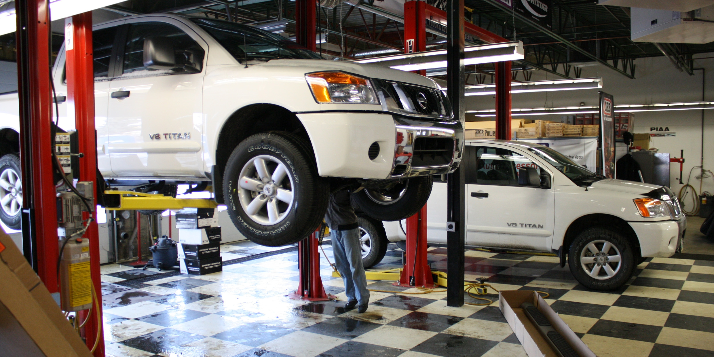 Cap It mechanic Nick Handspiker fits running boards to a pair of new Nissan Titans.