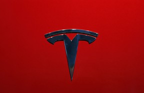 FILE- This Oct. 3, 2018, file photo shows the logo of Tesla Model 3 at the Auto show in Paris. U.S. securities investigators have subpoenaed information from Tesla about production forecasts for the Model 3 electric car that were made last year, the company acknowledged in a regulatory filing Friday, Nov. 2. The disclosure in Tesla's quarterly financial report also says the Securities and Exchange Commission subpoena covered other public statements made about Model 3 production. The filing also says Tesla is cooperating with a Justice Department request for information about production.