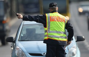 A policeman in Berlin pulls over a car caught speeding during a city-wide police action to catch people for speeding and other traffic infringements on April 16, 2013.