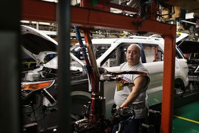 Tony Sada assembles a 2011 Ford Explorer at the Chicago Assembly Plant on December 1, 2010 in Chicago, Illinois.