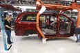 Workers on the production line at Chrysler's assembly plant in Windsor, Ont., work on one of their new minivans on January 18, 2011.