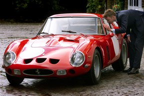 Simon Kidston, of Bonham and Brooks auction house, peers inside a vintage 1963 Ferrari 250 GTO which won the 1963 Le Mans GT race, in London, 30 October 2000.
