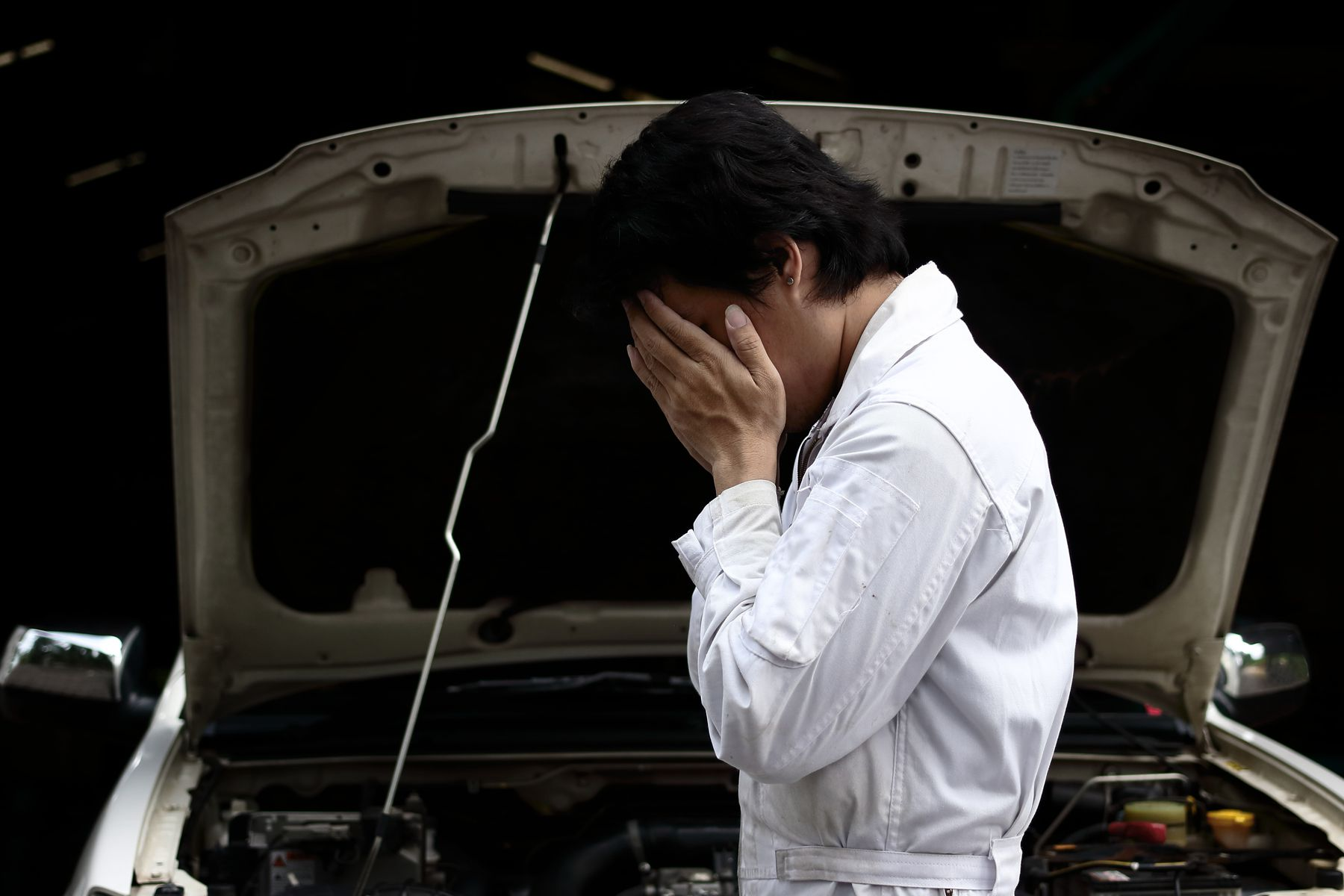 Frustrated stressed young mechanic man in white uniform covering face with hands with car in open hood at the garage. Auto repair service.