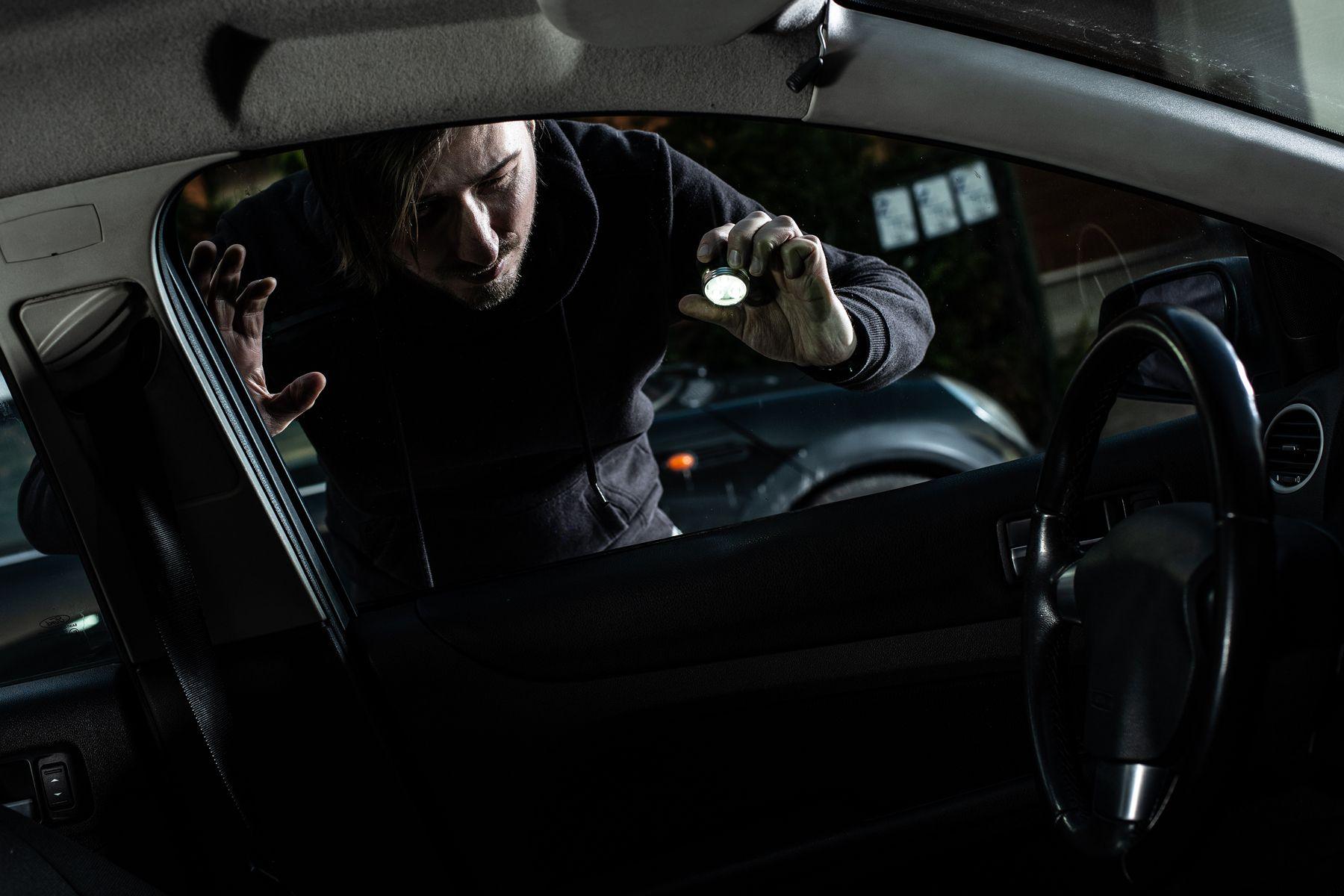 Masked thief in a balaclava looking to car interior