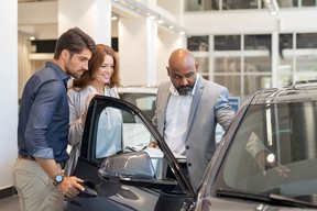 Salesman showing car features to couple