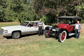 Neighbours Tom King and George Hoffman display their 1990 and 1914 models illustrating the evolution of Cadillac motor cars over a 75-year period.
