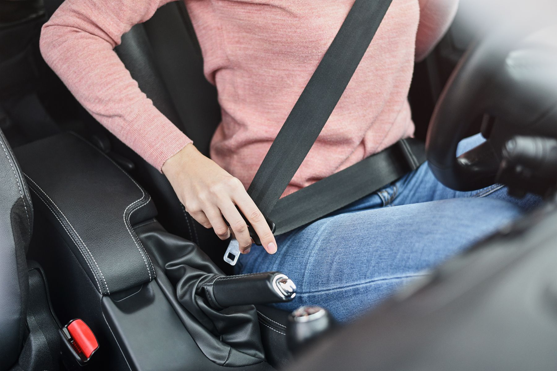 Woman fastening seat belt in the car. Car safety concept