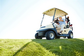 A senior retired couple driving a golf cart on a golf course
