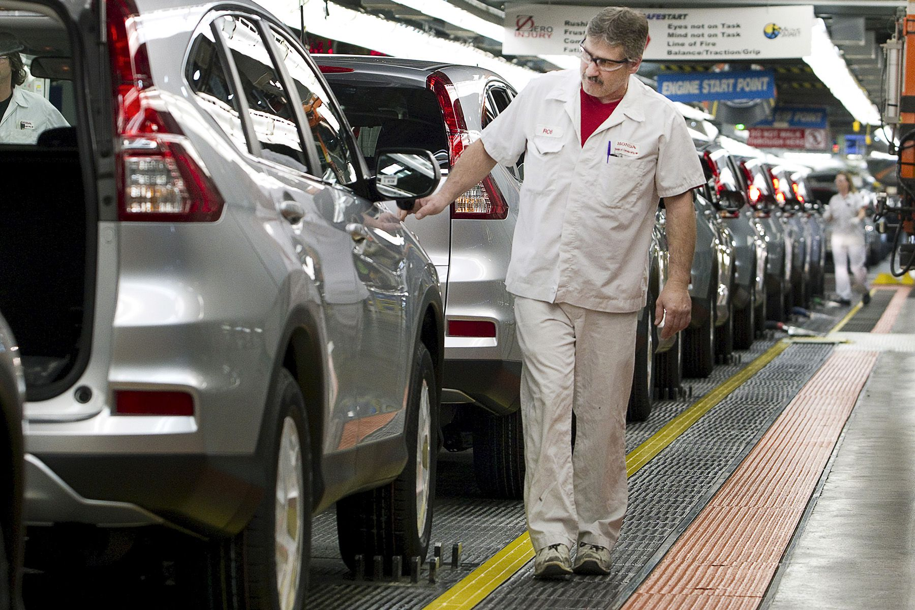 Production Associates inspect cars moving along assembly line at Honda manufacturing plant in Alliston, Ontario
