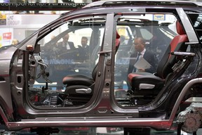 A visitor looks to a car model with components of the auto parts manufacturer 'Magna' at the 2017 Frankfurt Auto Show 'Internationale Automobil Ausstellung' (IAA) on September 13, 2017 in Frankfurt am Main, Germany.