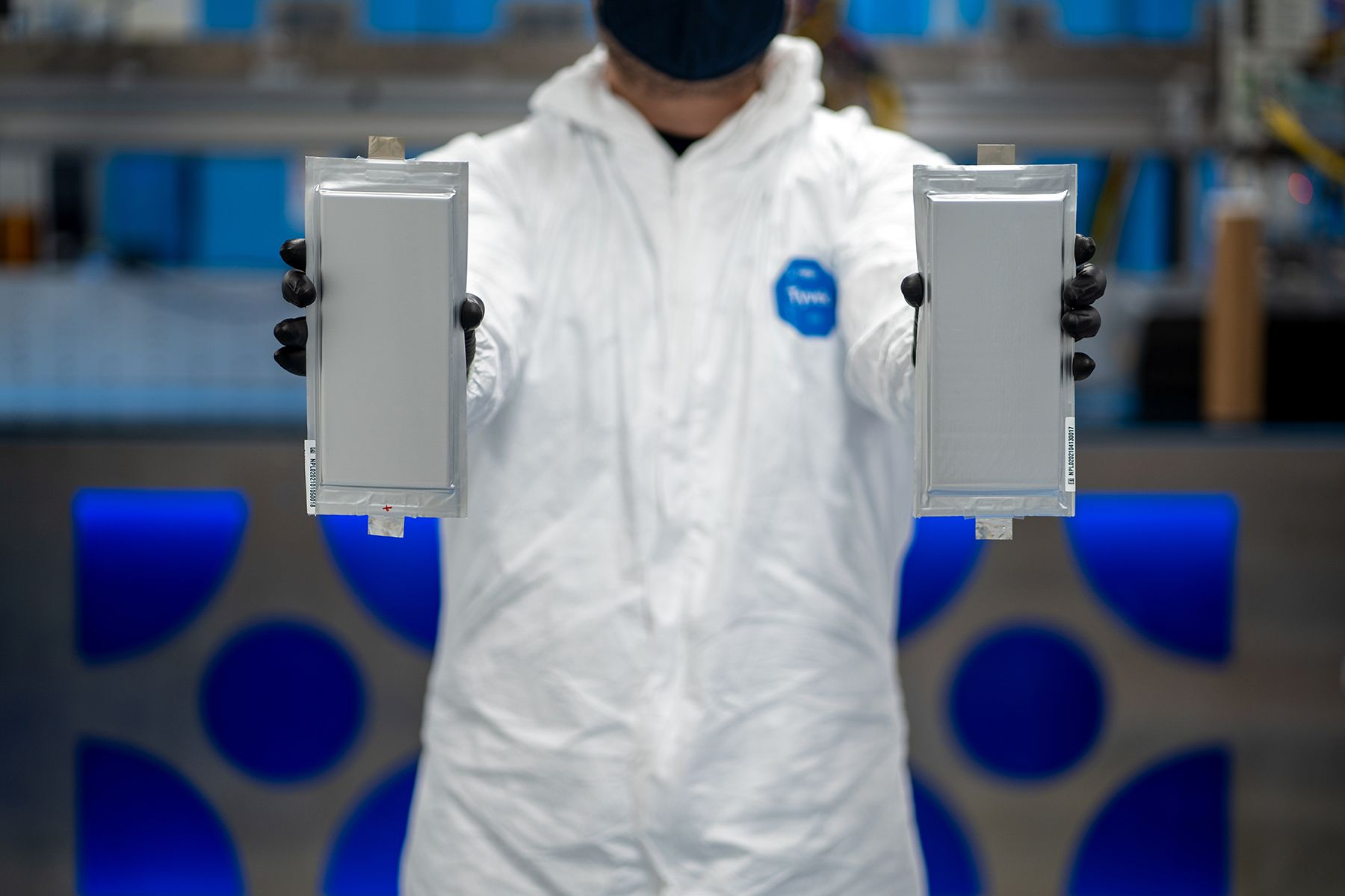 A Solid Power manufacturing engineer holds two 20 ampere hour (Ah) all solid-state battery cells for the BMW Group and Ford Motor Company