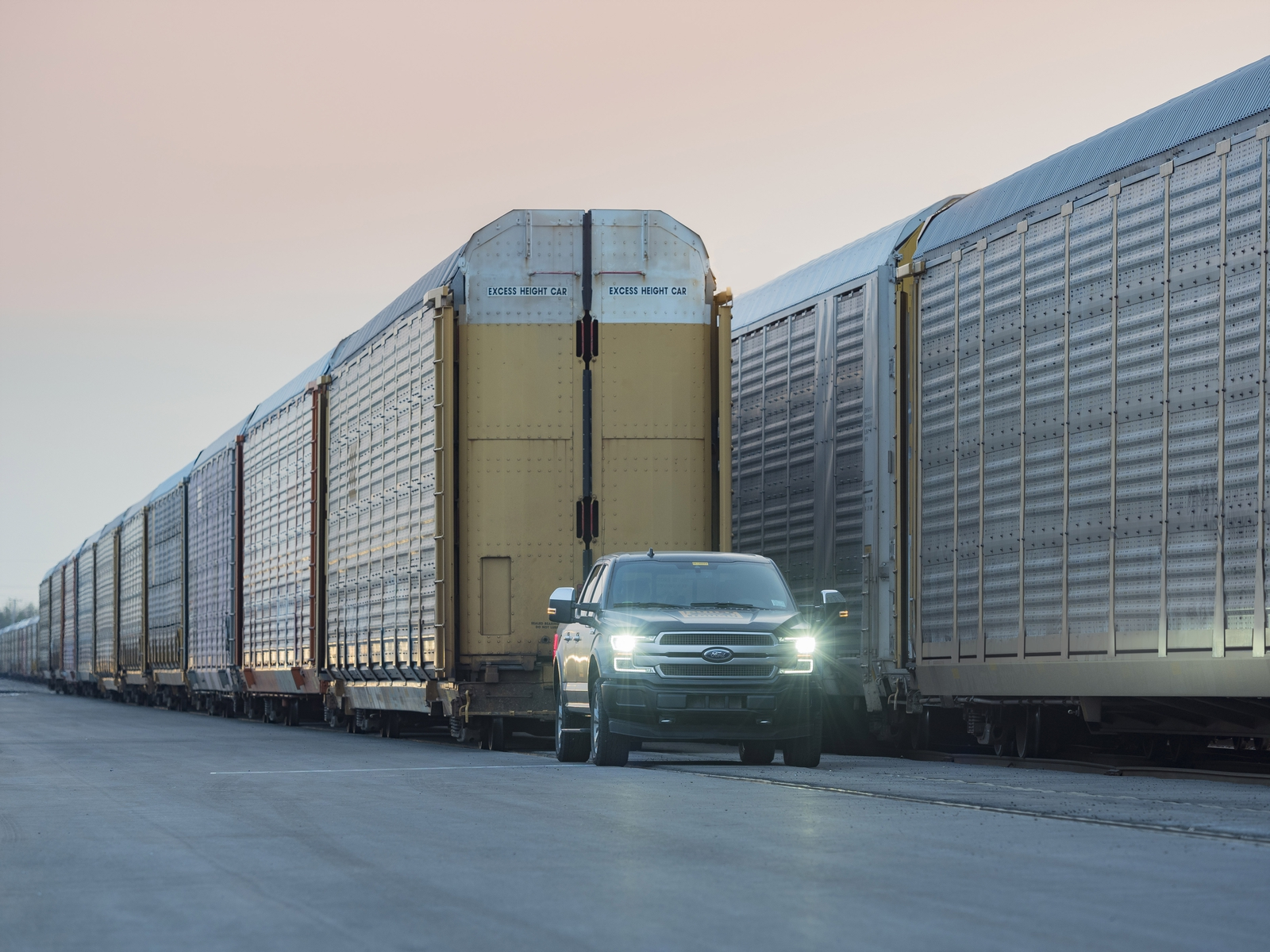 A prototype of the all-electric Ford F-150 Lightning pulls 10 rail cars loaded with 42 Ford trucks