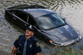 A Michigan State police officer investigates a car that is believe to have driven into the water on I-94 near the Livernois Avenue exit in Detroit on Monday, June 28, 2021.