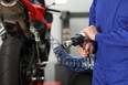 Close up of a motorcycle mechanic hand holding a pneumatic gun in a mechanical workshop