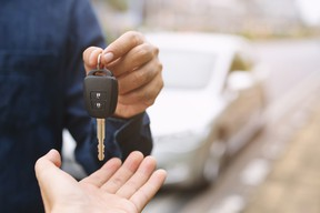 A car seller handing over the keys to a used car to a buyer.