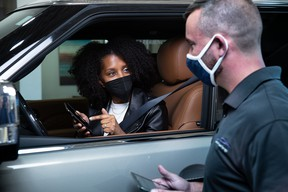 An Infiniti customer speaking with a dealership employee about phone and infotainment system compatibility