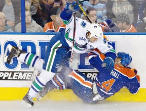 Vancouver Canucks' Andrew Alberts, 41, checks Edmonton Oilers Taylor Hall, 4, during first period pre-season NHL hockey action in Edmonton, Alta., on Saturday September 21, 2013. THE CANADIAN PRESS/Jason Franson