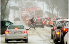 A pedestrian crosses the street on River Valley Road while traffic sits at a stand-still due to slippery road conditions and heavy snowfall in Edmonton on Nov. 27, 2014.