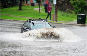 Vehicles drive through a flooded road at 102nd Street and 100th Avenue because of heavy rainfall in Edmonton, July 25, 2014.