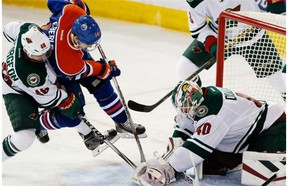 Minnesota Wild's Jared Spurgeon upends Edmonton Oilers' Jordan Eberle as he tries to get the puck from the glove of goalie Devan Dubnyk during NHL action on January 27, 2015 in Edmonton.