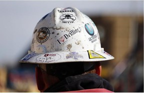 In this March 25, 2014 photo, a worker wears a protective helmet decorated with stickers during a hydraulic fracturing operation at a gas well near Mead, Colo.