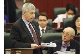 Alberta Health Minister Stephen Mandel (right) listens to Robin Campbell (left), Alberta Minister of Finance, deliver the provincial budget speech at the Alberta Legislature on March 26, 2015.