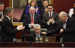 Robin Campbell (left), Alberta Minister of Finance, is congratulated by Alberta Health Minister Stephen Mandel (right) after Campbell delivered the provincial budget speech at the Alberta Legislature on March 26, 2015.