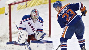 Cam Talbot makes a save on Matt Hendricks on March 30, 2014.