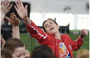 Canada's Christine Sinclair exchanges high fives with players from the U-12 Red Deer Renegades during a skills camp prior to the unveiling of a Canada Post Team Canada soccer stamp at the Commonwealth Stadium Community Recreation Centre on Tuesday.