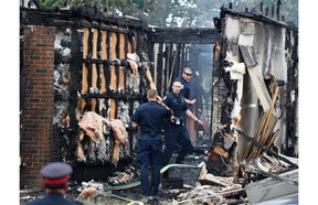 Police officers investigate at the scene of the burned out house at 18620-62A Ave. where Const. Daniel Woodall was killed while trying to serve a warrant on Monday.