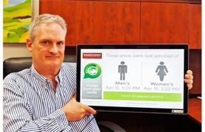 John Putters, CEO of Visionstate, demonstrates the company's touch panel for tracking washroom maintenance.