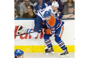 Justin Schultz of the Edmonton Oilers checks Leo Komarov of the Toronto Maple Leafs into the boards during an NHL game at Rexall Place on March 16, 2015.