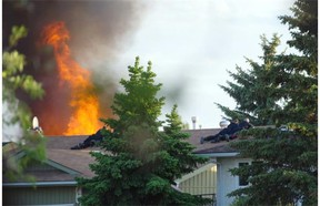 Police surround a burning house following a shooting near 186 St. and 62A Ave. in Edmonton on June 8, 2015.
