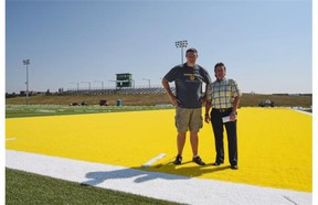 University of Alberta Golden Bears football head coach Chris Morris, left, and Cheryl Harwardt, director of operations for the faculty of physical education and recreation, stand on the new turf at Foote Field on July 9, 2015.