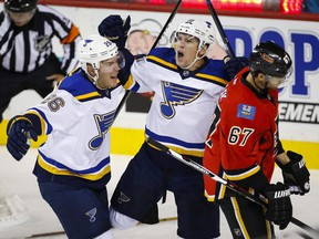 St. Louis Blues' Scottie Upshall, center, celebrates his goal with teammate Paul Stastny, left, as Calgary Flames' Michael Frolik, from the Czech Republic, skates by during the first period of an NHL hockey game Tuesday, Oct. 13, 2015, in Calgary.