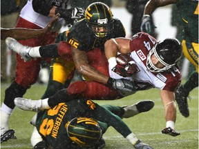 Edmonton Eskimos linebacker Dexter McCoil, top, and Willie Jefferson take down Calgary Stampeders running back Matt Walter during a Canadian Football League game at Commonwealth Stadium on Sept. 12, 2015.