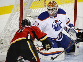Edmonton Oliers' goaltender Cam Talbot, right, blocks the net on a shot from Calgary Flames' Kris Russell (4) during first period NHL hockey action in Calgary on Saturday, Oct. 17, 2015.