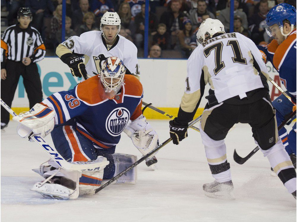 Anders Nilsson of the Edmonton Oilers, throws out a rebound past Evgeni Malkin of the Pittsburgh Penguins at Rexall Place in Edmonton.