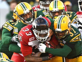 Edmonton Eskimos' Otha Foster (37), Marcell Young (23) and Dexter McCoil (45) stack up Calgary Stampeders' Jerome Messam (33) during the CFL West Division final at Commonwealth Stadium in Edmonton on Sunday.