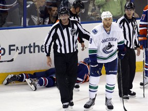 Vancouver Canucks' Zack Kassian heads to the penalty box after breaking former Edmonton Oilers forward Sam Gagner's jaw with his stick during an NHL exhibition game on Sept. 21, 2013 at Rexall Place.  Kassian plays his first game in an Oilers uniform on Thursday.