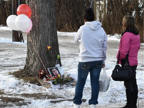 People stop by a memorial set up after a man died following an altercation behind Duster's Pub at 118th Ave. and 64th St. early on Dec. 3 in Edmonton.