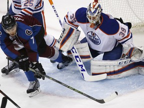 Colorado Avalanche centre John Mitchell, left, uses his stick to sweep the puck toward Edmonton Oilers goalie Anders Nilsson on Dec. 19, 2015, in Denver.