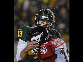 Edmonton Eskimos quarterback Mike Reilly (13) gets hit by Calgary Stampeders' Juwan Simpson during CFL action at Commonwealth Stadium on Sept. 12, 2015.